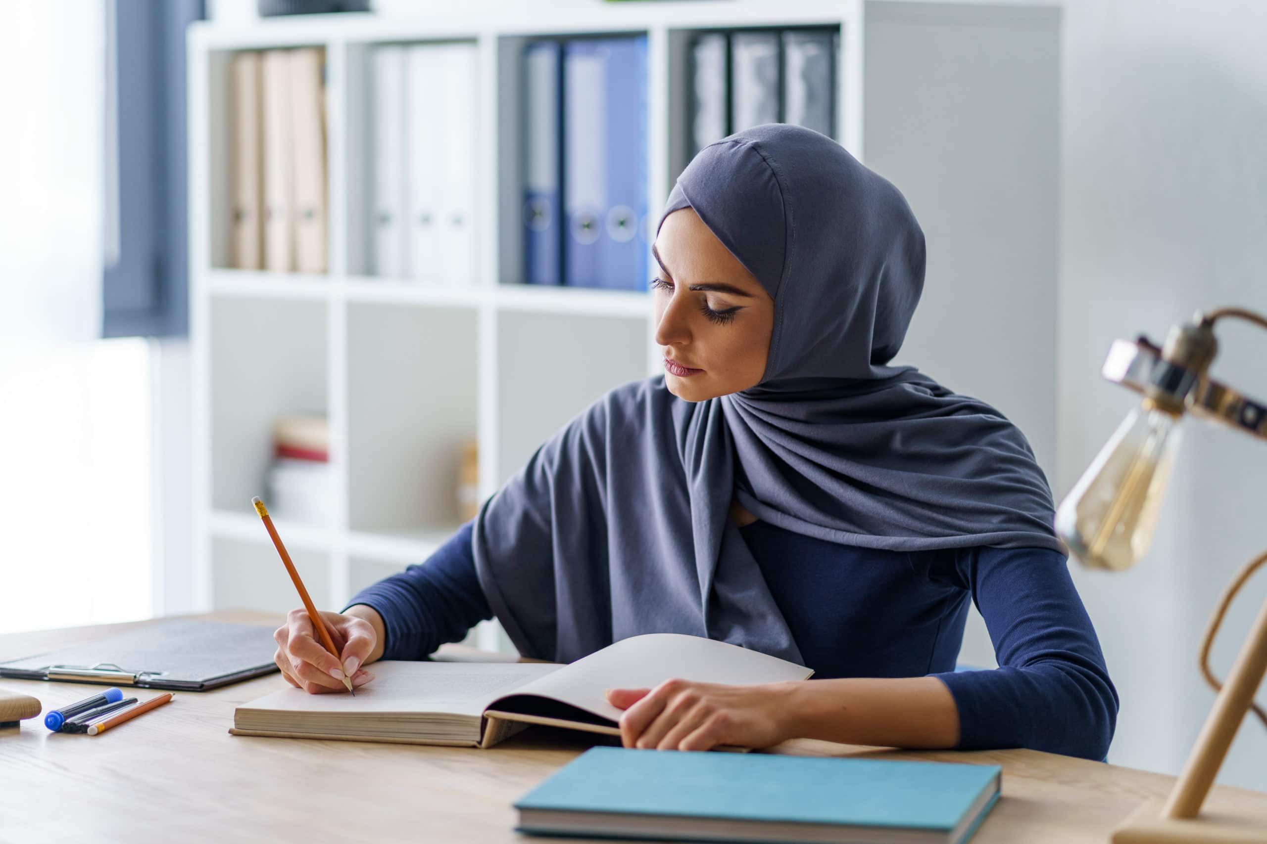 Female Muslim professor taking a note in a book, getting ready for classes. Woman fully absorbed in work.
