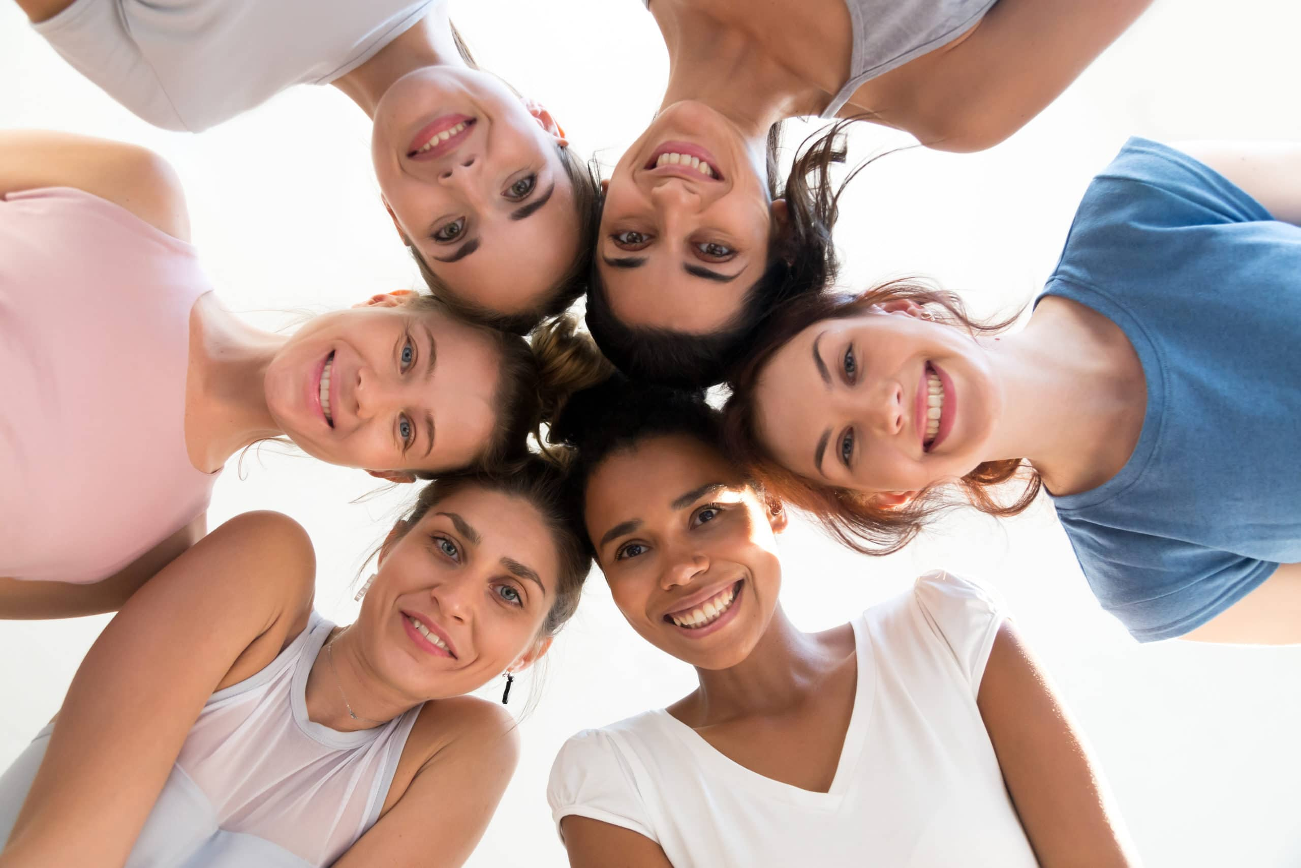 Diverse group of sporty attractive girls enjoy time together, smiling people in sportswear after yoga lesson, mixed race female students, happy friends looking at camera. Well being, wellness concept