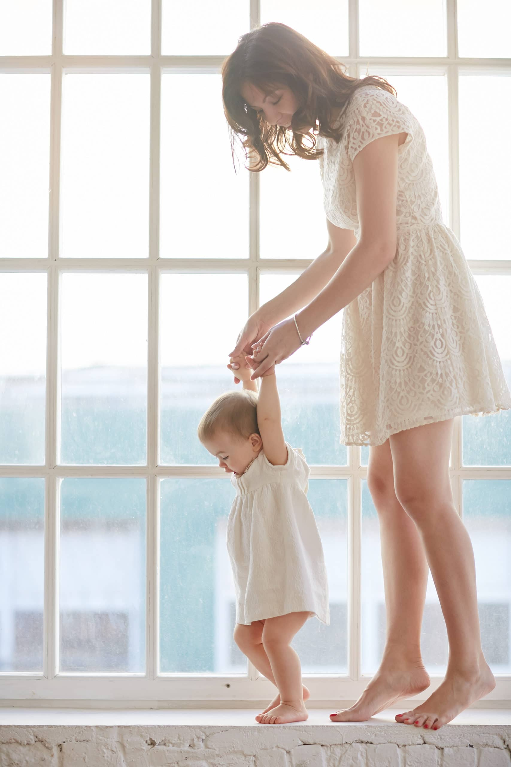 Baby taking first steps with mother's help at home. Baby leaning walking with mother