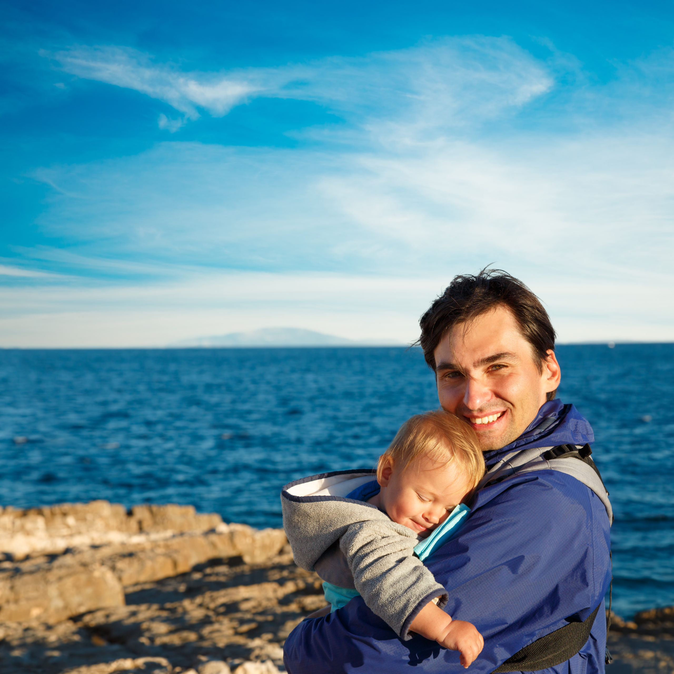 Happy,Father,With,His,Little,Son,In,Carrier,On,Sea