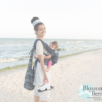 Lady carrying baby while walking on a beach