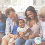 Picture of parents and grandparents holding baby on their lap