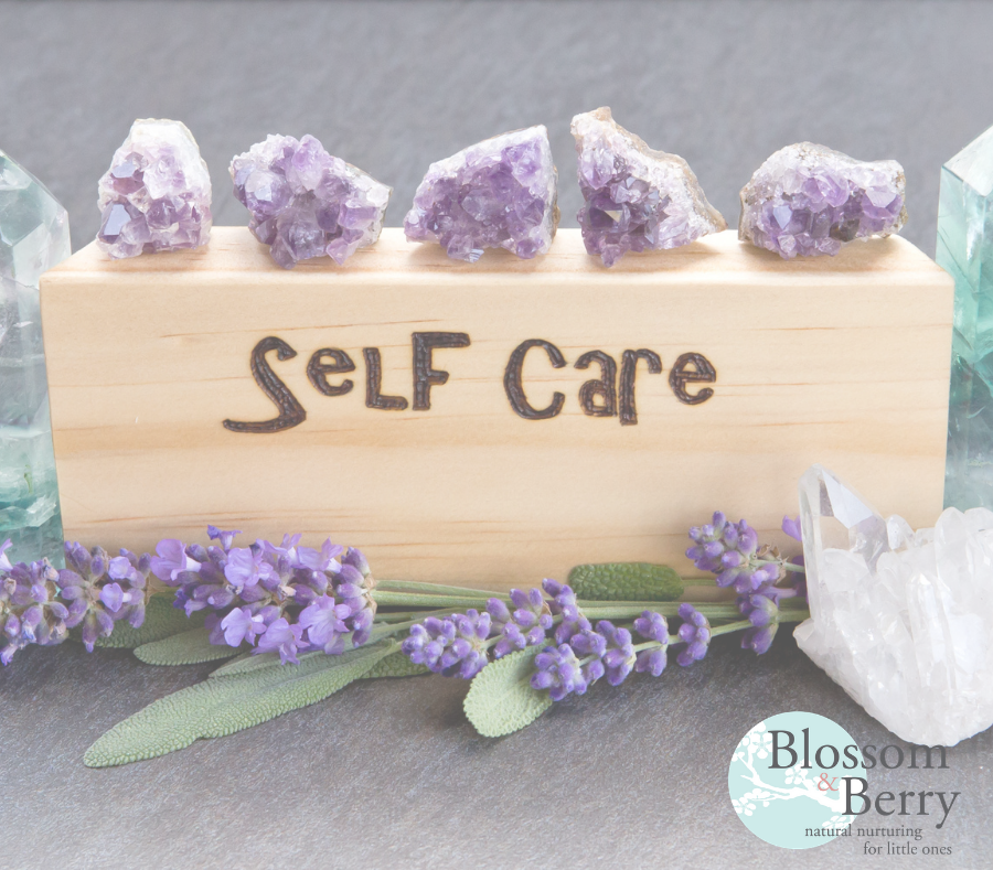 Picture of a piece of wood with the word self care on surrounded by crystals and flowers