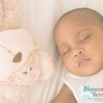 Picture of a baby sleeping next to a teddy bear