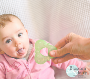 Picture of a baby poking their tongue out and being handed a teething toy