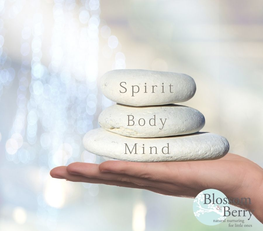 Picture of a hand holding 3 stones with the words spirit body and mind on each